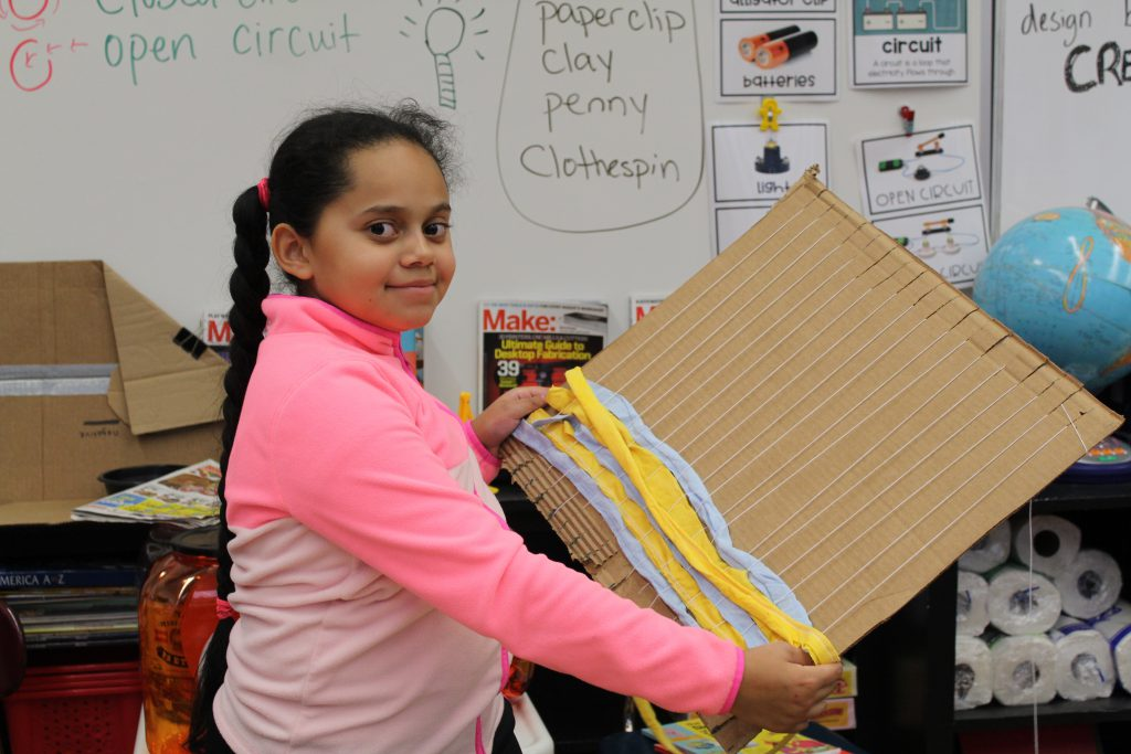 A student wearing a bright pink long sleeved shirt stands tall and displays her project: a weaving loom made from a piece of cardboard, string and scraps of tee shirts.