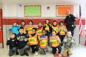 A group of students wearing orange and yellow safety vest pose in a photo with school resource officer Devin Brust.