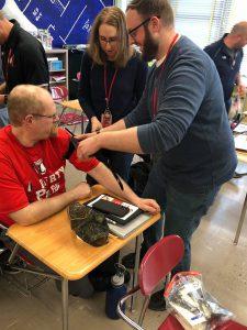 Two teachers tie a tourniquet to another teacher
