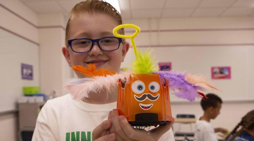 An elementary boy hold a small orange robot