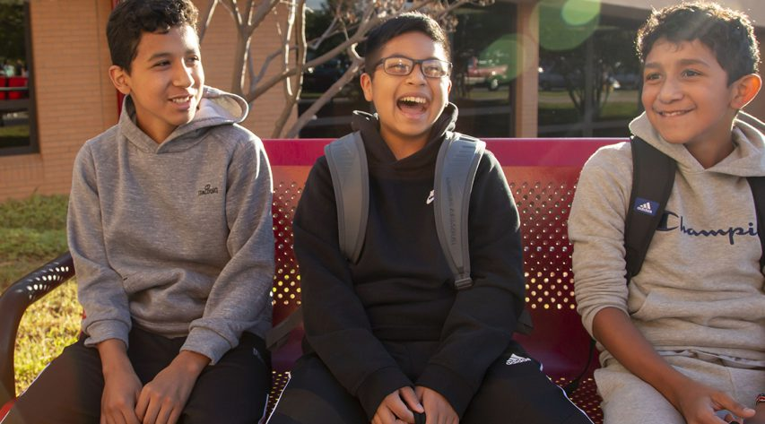 three boys on a bench outside