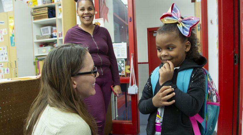 a teacher bends down to talk with a kindergarten girfl