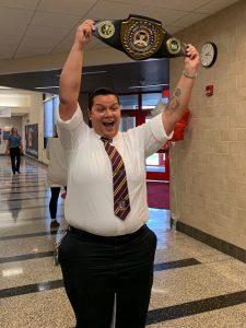 A teacher holds a championship belt over her head