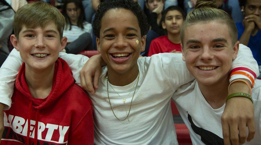 The boys sittting in bleachers smiling
