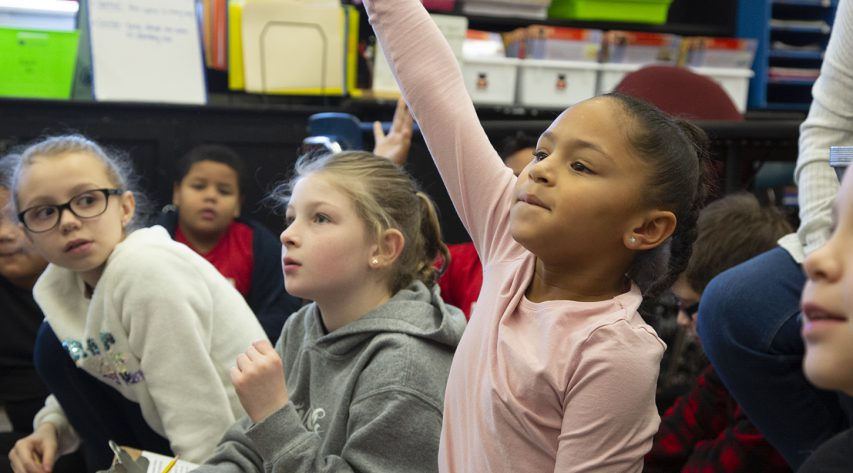 a student raises her hand to answer a question