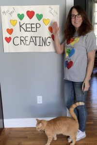 "A woman stand by a sign that says ""Keep Creating"" with a red cat at her feet"