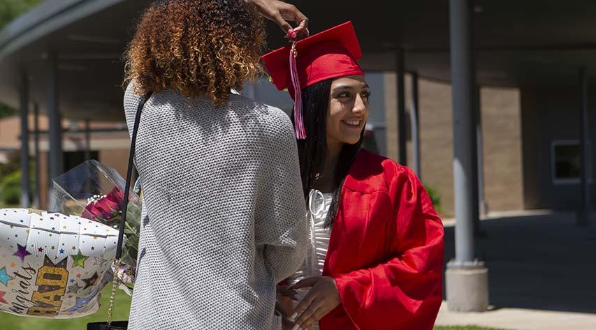 A woman adjusts a tassel on a graduate's cap