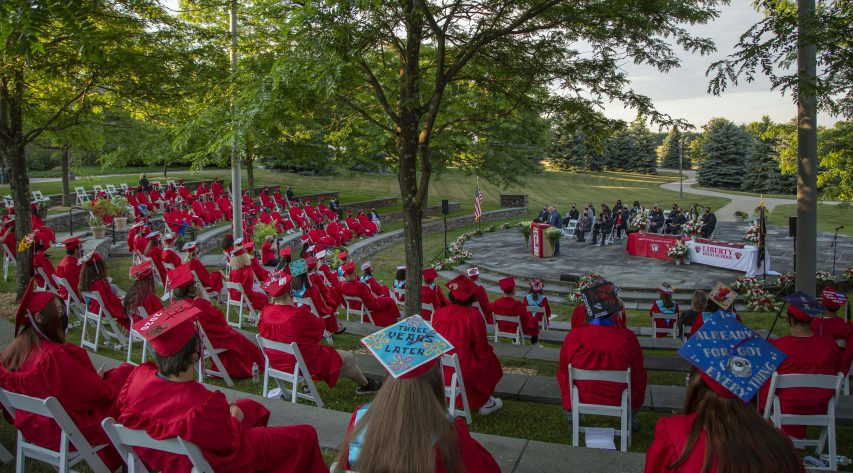 A graduation scene with scores of graduates in red robes seated in the round, outdoors, facing a stage