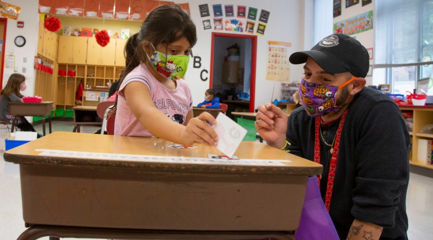 A teacher crouches next to a young student's desk to help with letters