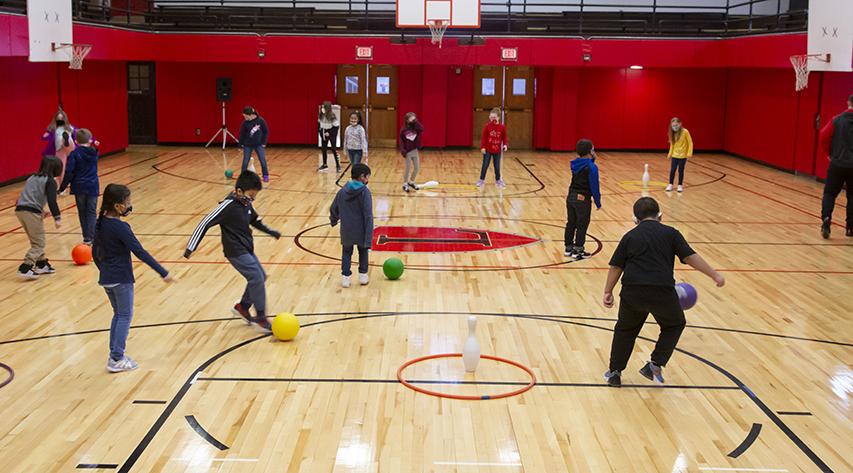 Children kick multi-colored balls in a gymnasium