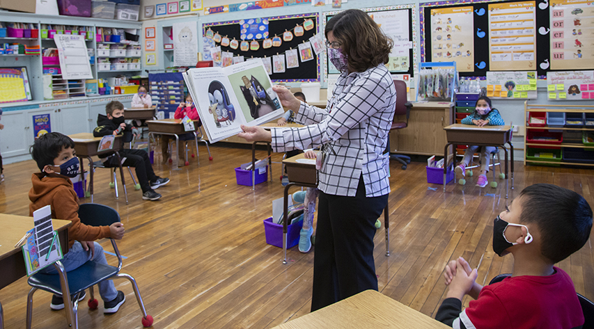 A teacher in a classroom reads a picture book to young students as she walks from desk to desk, holding the book open so the students can see the pictures