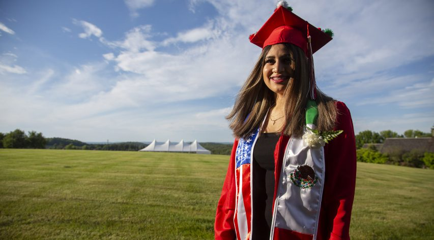 A graduate stands in a field and smiles