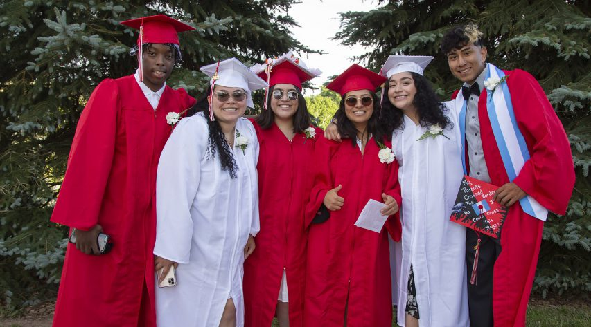 Six graduates in red and white gowns smile in a group portrait