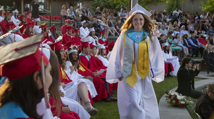 A graduate walks past rows of seated students in caps and gowns