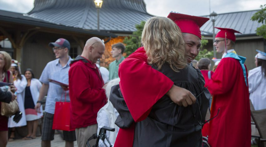 A graduate and teacher hug