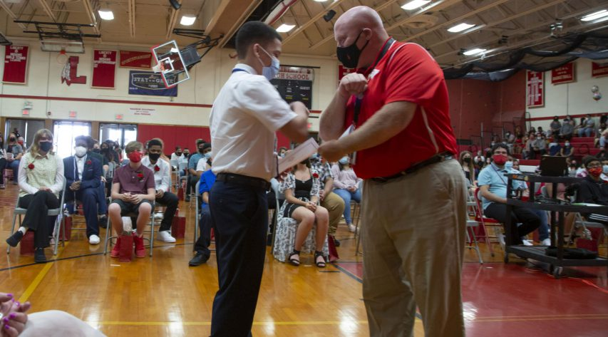 A teacher and a student bump elbows as the teacher hands the student a certificate